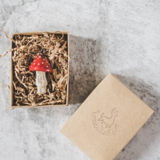 Rankų darbo Kalėdų eglutės žaisliukas musmirė. Kalėdinė dekoracija supakuota dovanų dėžutėje. Pagaminta Murdeko keramikos studijoje.