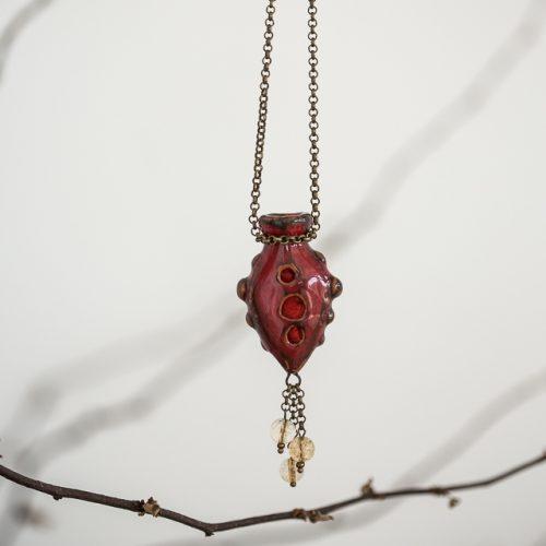 Raudonas pakabukas kimštas natūralia vilna, kuri ilgai išlaiko kvapus. Papuošalas pildomas eteriniu aliejumi ar kvepalais.